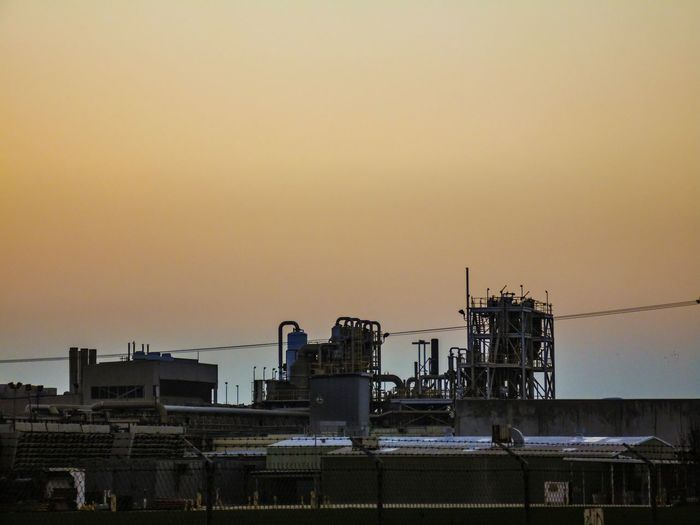 Exterior of factory against clear sky during sunset