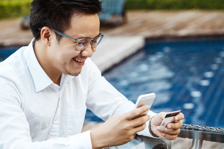 Young man using mobile phone in swimming pool
