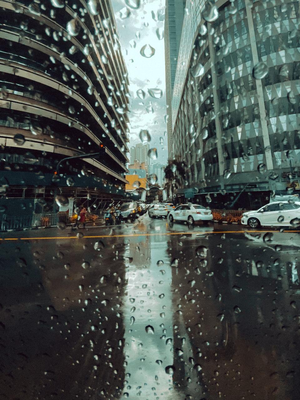 CITY STREET SEEN THROUGH WET WINDOW