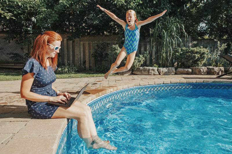 Woman using laptop while girl jumping in swimming pool