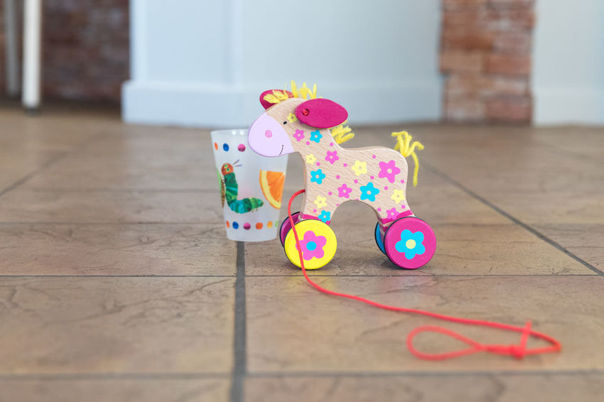 Colorful wooden toy horse with red leash on tiled floor Fun Textured  Animal Representation Animal Themes Childhood Close-up Day Disposable Cup Flooring Floral Pattern Focus On Foreground Horse Indoors  Multi Colored Pattern Pet Leash Pink Color Plastic Selective Focus Still Life Tiled Floor Toy Two Objects Wood - Material Yellow