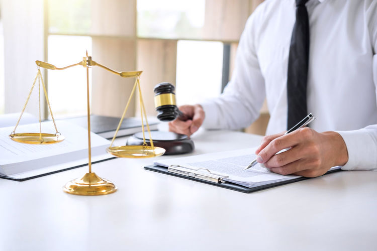 Midsection Of Male Lawyer Writing On Document At Desk In Office