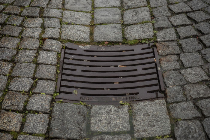 Drain cover in the middle of a road City Drain Cover Rain Road Underground Architecture Canal Clean Day Dirty Ground No People Outdoors Sanitation Street Streetphotography System Town Urban Water Watercourse