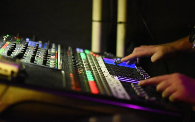 Cropped hands of man playing sound mixer at nightclub