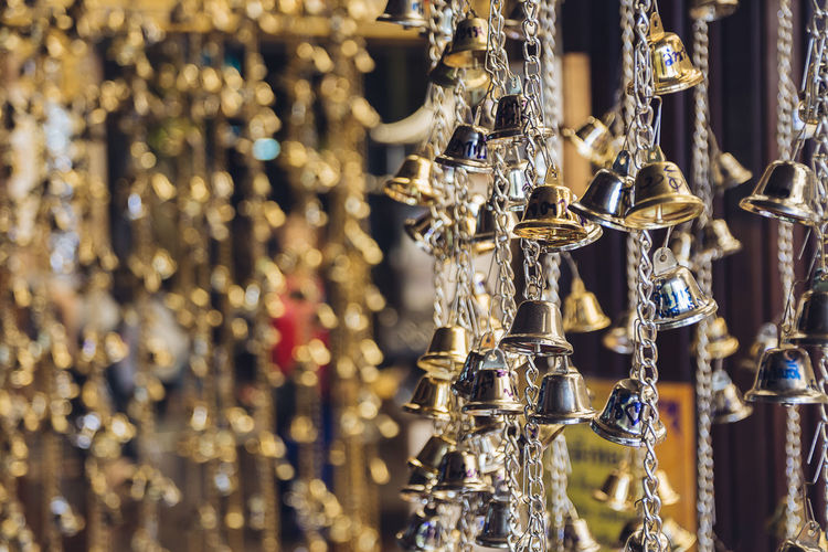 Close-up of bells hanging for sale in market