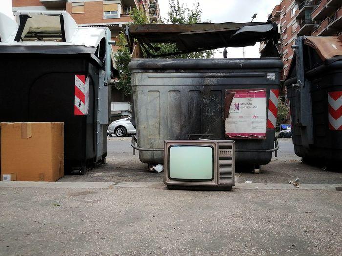 Garbage bin by street in city