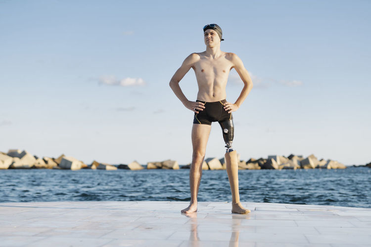 Full length of shirtless man standing at beach against sky