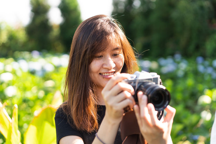 Photographer Photography Woman Portrait Thai Japan Asian, White, Chocolate Aka Cheetah Girls Headshot One Person Photography Themes Holding Camera - Photographic Equipment Real People Photographing Smiling Hairstyle Young Adult Front View Adult Looking At Camera Women Focus On Foreground Leisure Activity Photographic Equipment Technology Young Women Hair Outdoors Digital Camera Beautiful Woman
