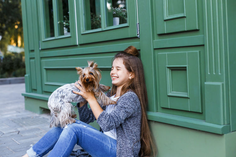 Happy Girl Holding Dog While Sitting By Store In City