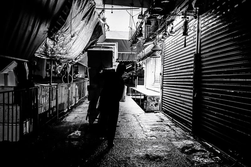 Man standing on alley amidst buildings in city