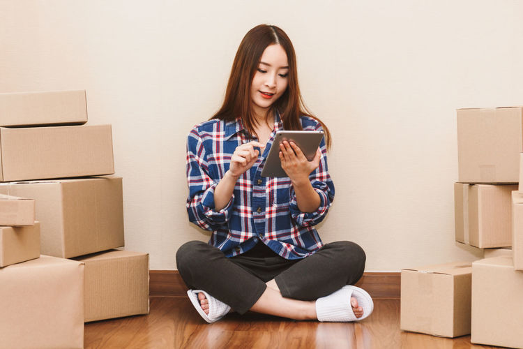 Young woman with cardboard box at home - Business online and delivery concept Adult Beginnings Box Box - Container Cardboard Cardboard Box Communication Connection Flooring Front View Full Length Holding Indoors  Mobile Phone Moving House One Person Packing Sitting Technology Wireless Technology Wood Young Adult Young Women