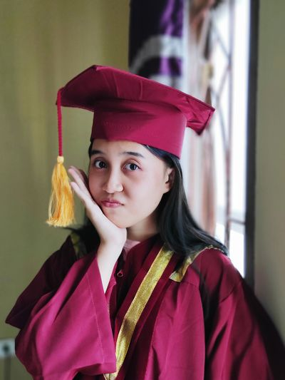 Portrait of young woman wearing graduation gown