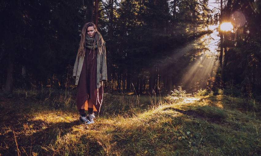Full length of woman with dreadlocks standing in forest