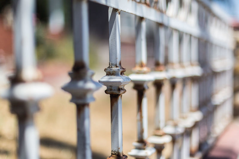 Rusted wrought iron fence Fence Focus On Foreground Garden House Iron Fence Metal Old Old And Rusted Rusted Rusted Wrought Iron Fence Shaded Shallow Depth Of Field Street Trees Wall White Paint