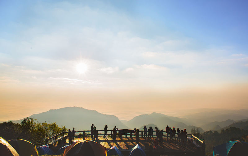 People at observation point against sky during sunset