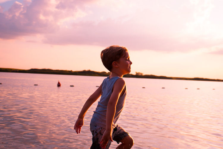 Feeling free in summer by the water. Happy Freedom Running Beach Boys Carefree Caucasian Child Childhood Enjoyment Innocence Kid Leisure Activity Lifestyles Males  Motion Nature One Person Outdoors Playful Real People Scenics - Nature Sea Sky Sunset Water Horizon Over Water
