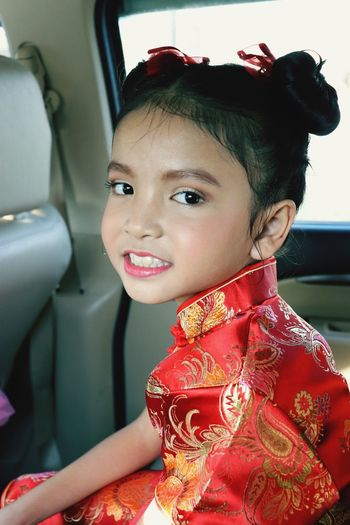 Portrait of smiling cute girl wearing traditional clothing while sitting in car