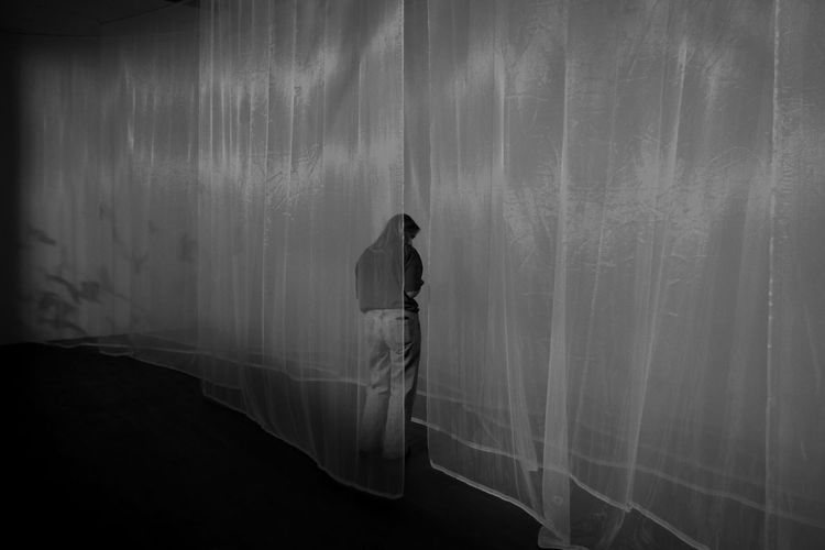 Rear view of woman standing by curtain