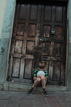 child with a globe in a sad moment Awaiting Doors Architecture Blond Hair Building Exterior Built Structure Casual Clothing Childhood Day Door Full Length Girls Leisure Activity Lifestyles One Person Outdoors People Real People Sad Sad & Lonely Sad Face Sadness Sitting Window