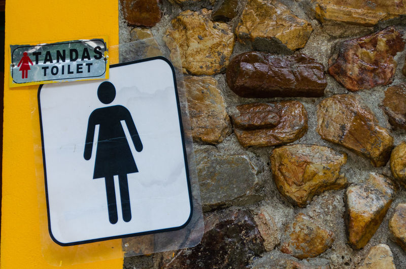 Close-up of toilet sign on wall