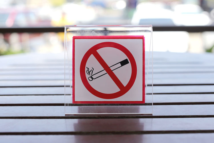 Signs of no smoking on the table in restaurant. Sign Communication Warning Sign Forbidden Cigarette  Information Information Sign No Smoking Sign Smoking Issues No People Focus On Foreground Red Close-up Safety Protection Social Issues Warning Symbol Shape Security Selective Focus Exclusion Information Symbol