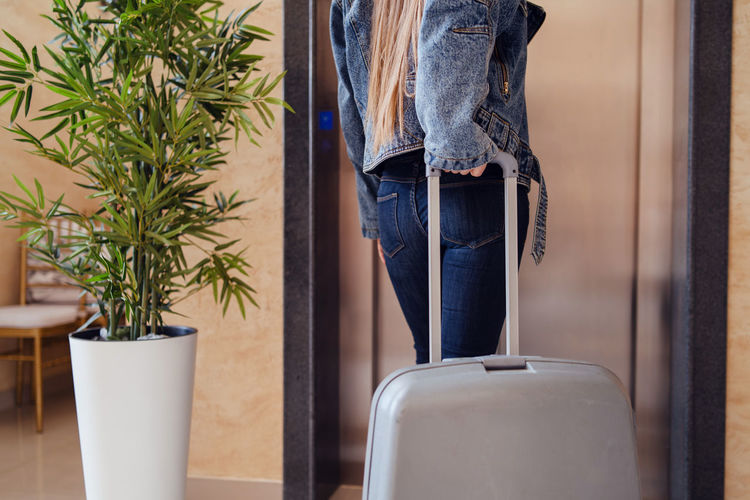 Mid section of woman holding suitcase standing by potted plants hotel