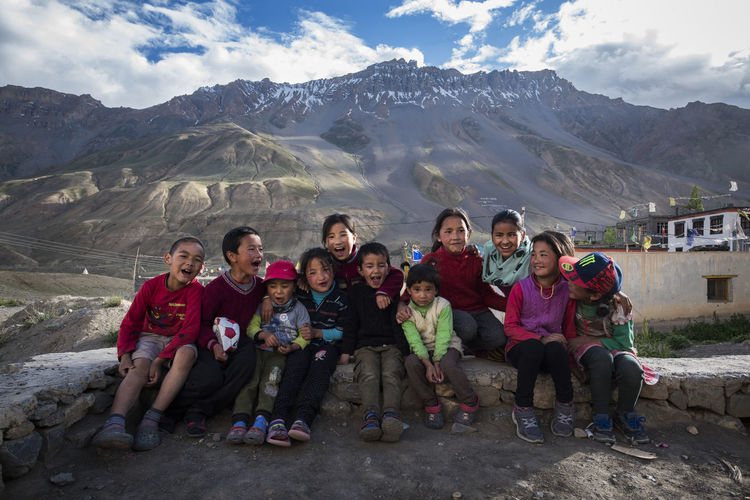 Portrait of happy friends sitting on mountain against sky