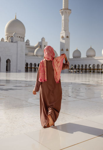 Rear view of woman walking at sheikh zayed mosque during sunny day