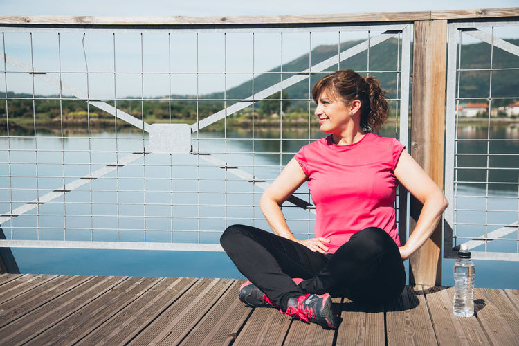 Tired woman sitting on footbridge during sunny day