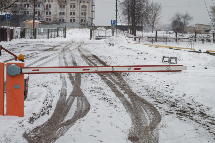 Winter road with tyre print and red entrance barrier Architecture Barrier Building Exterior Built Structure City Cold Temperature Day Lamp Nature No People Outdoors Pass Permission Permit Pole Red Snow Snowing Transportation Weather Winter EyeEmNewHere The Baltics