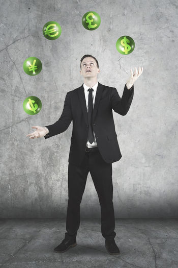 Businessman Juggling Currency Symbols Against Wall