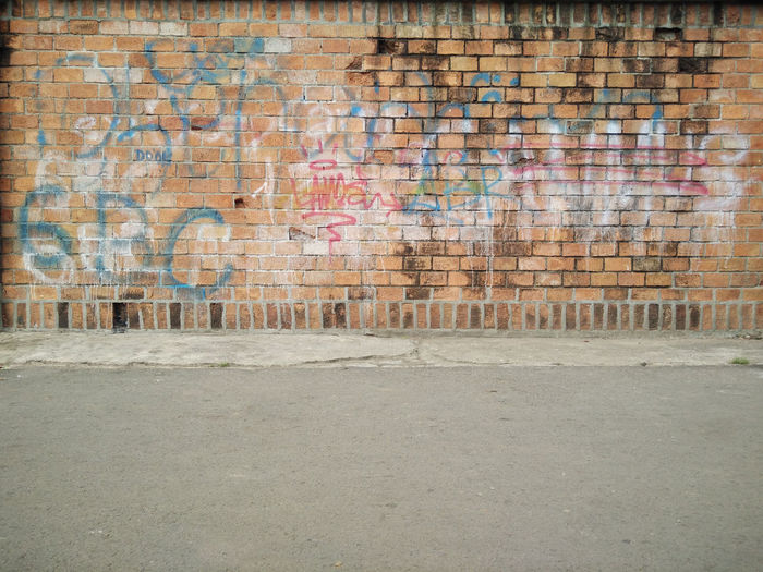 frontal view of brick wall vandaliszed Background For Deskto Background For Fashi Backgrounds Brick Wall Brick Wall Built Structure City Day No People Outdoors Simplicity Vandalism Wall - Building Feature