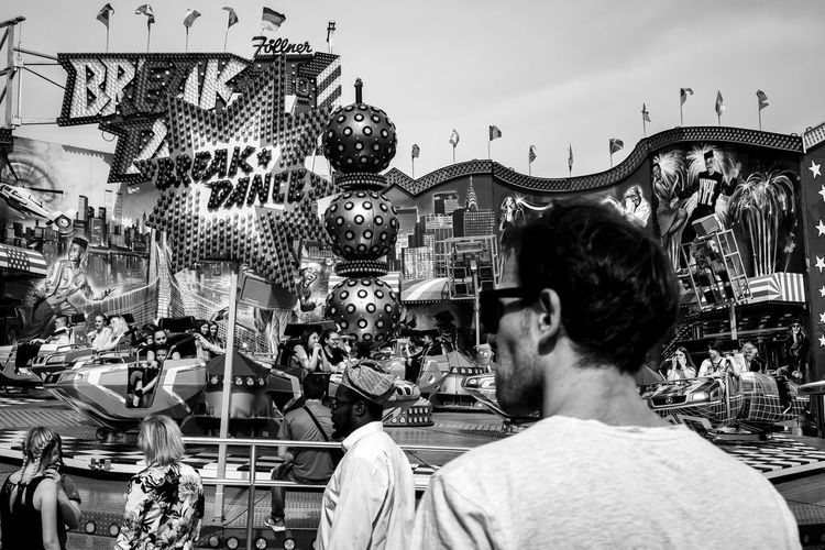 Rummelplatz ... Urban Perspectives Street Photography Monochrome Black & White Amusement Park Ride Black And White Real People Rear View Men One Person Built Structure Lifestyles Building Exterior City Day Leisure Activity Retail  Adult Headshot Sky Portrait City Life Waist Up Street Market Crowd The Devil's In The Detail The Street Photographer - 2019 EyeEm Awards