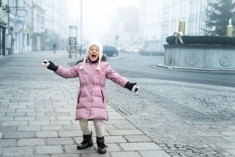 Woman with arms outstretched standing in city