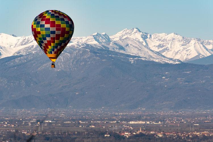Hot air balloon flying over mountain against sky