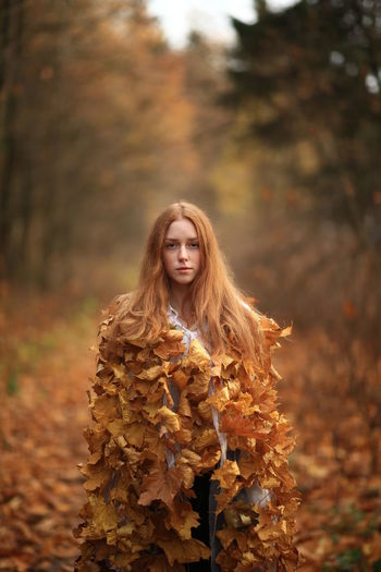 Portrait of young woman covered with leaves standing at forest during autumn