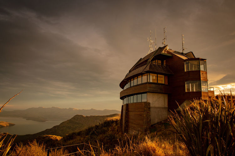The gondola building high up on the hilltop is lit up at golden hour before sunset Sunset_collection Architecture Beauty In Nature Building Building Exterior Built Structure Christchurch Gondola Cloud - Sky Field Golden Hour Hilltop Land Landscape Low Angle View Mountain Nature New Zealand No People Outdoors Plant Scenics - Nature Sky Sunset Tower Tranquility