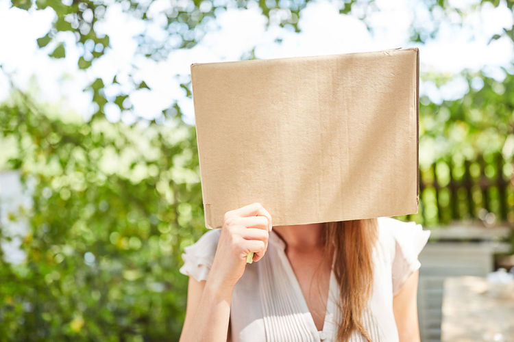 Close-up of woman covering face with cardboard box at park