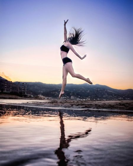 Full length of woman dancing at beach against sky during sunset