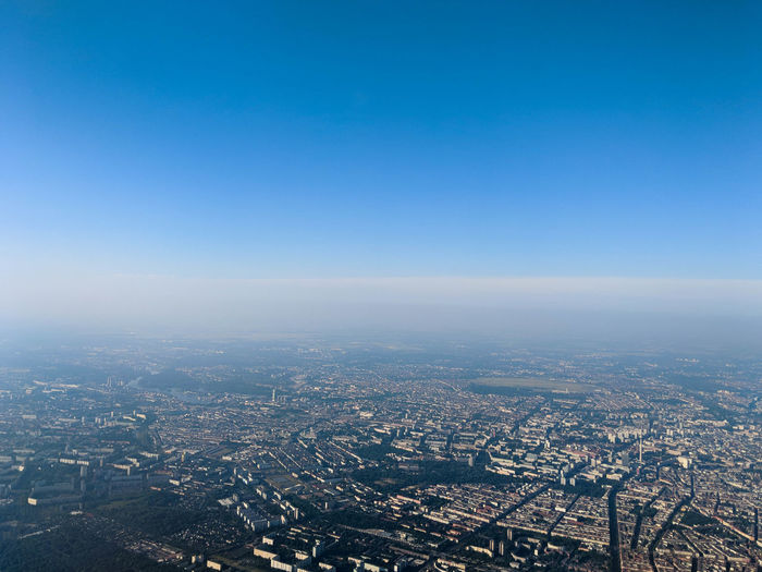 high angle view of city against clear blue sky Aerial View Architecture Blue Building Building Exterior Built Structure City Cityscape Clear Sky Copy Space Crowd Crowded Day Environment High Angle View Horizon Nature Outdoors Pollution Residential District Sky