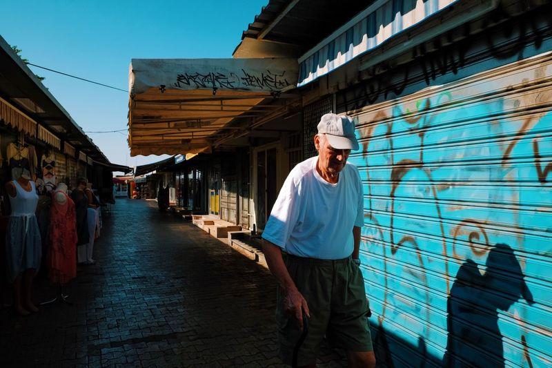Man standing on sidewalk in city