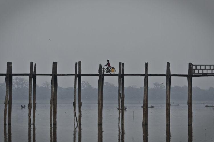 Man riding bicycle on bridge over lake