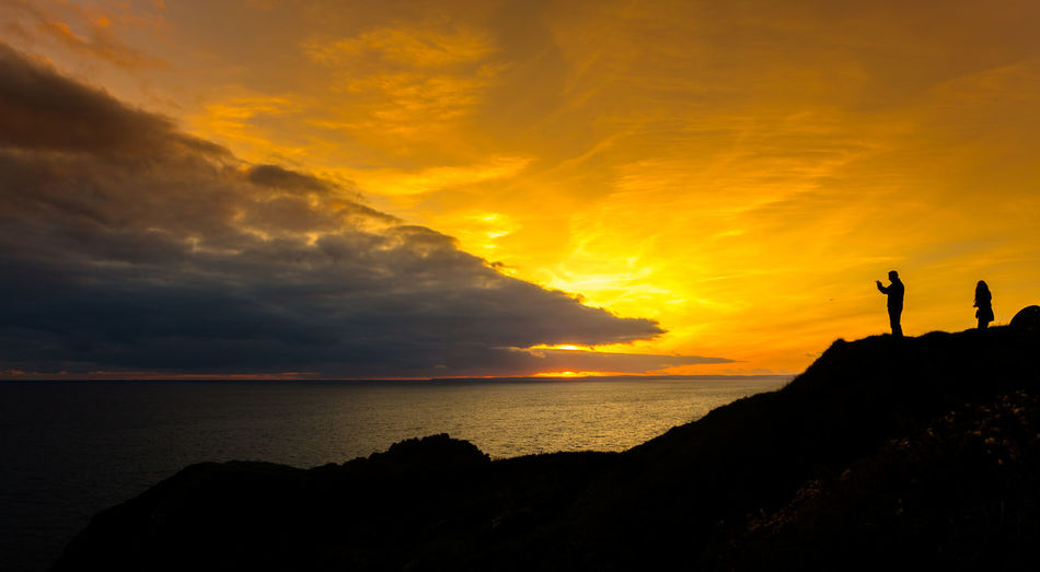 Watching the sunset unfold at Mullion Cove on the beautiful Cornish Coast. Beach Beauty In Nature Cloud - Sky Cornwall Uk Horizon Over Water Mullion Cove Nature Outdoors People Real People Scenics Sea Silhouette Sky Sunset Togetherness Tranquil Scene Tranquility Two People Water