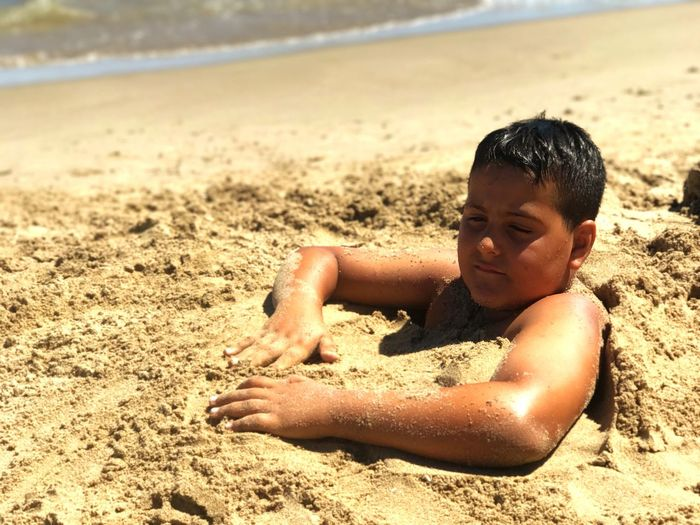 Close-up of boy on sand at beach