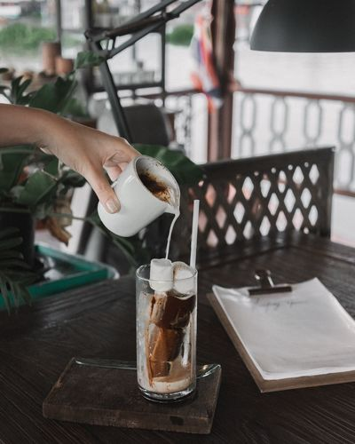 Close-up of hand pouring coffee in glass with marshmallows on table
