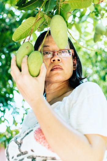 Portrait of woman holding mango growing on tree