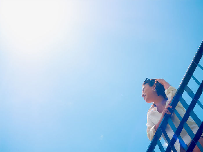 Low angle view of woman standing by railing against clear blue sky