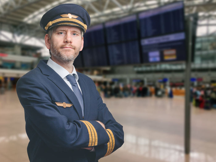 Portrait of pilot standing at airport