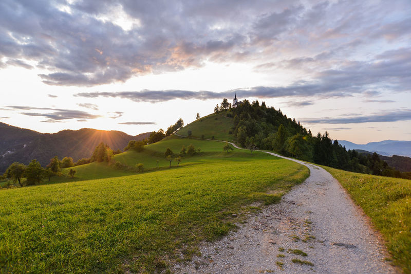 Just near my home in Ljubljana, there is a perfect hill to cool yourself in hot summer evenings. It's calle Sveti Jakob (Sanit Jacob in english) and pictures of that hill with church you have probably see in past. Very nice. Church Saint Jacob Summer Exploratorium Summertime Sunlight Sunset_collection Sveti Jakob The Great Outdoors - 2018 EyeEm Awards The Traveler - 2018 EyeEm Awards Beauty In Nature Church Architecture Cloud - Sky Environment Eveneings Grass Green Color Land Landscape Lens Flare Mountain Mountain Range Nature No People Non-urban Scene Outdoors Plant Religion Religious  Religious Architecture Road Scenics - Nature Sky Summer Sun Sunset Tranquil Scene Tranquility Transportation