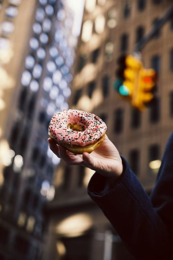 Close-Up Of Hand Holding Donut Against Buildings
